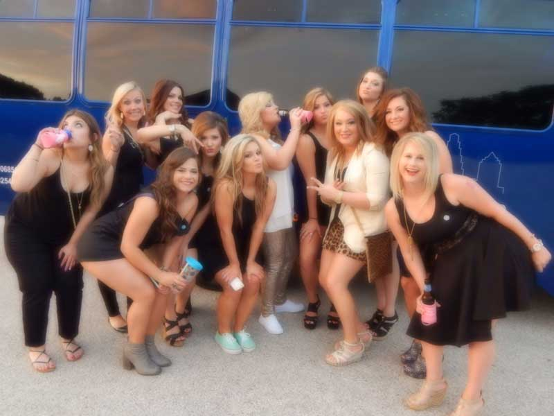 Group of girls in front of the party bus heading to rainy street in Austin, Texas.