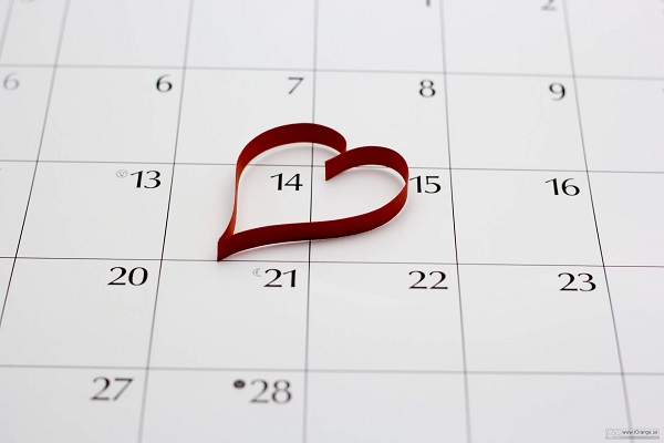 metal heart on a calendar directly over the 14th of February Valentine's Day.