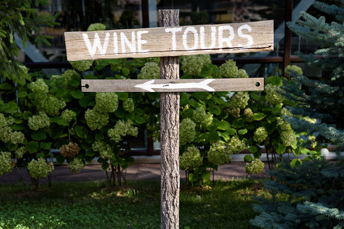 wooden sign giving directions to wine tours.